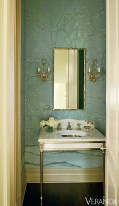 Delicate wallpaper strikes a feminine note in this bathroom.