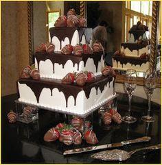 Three tier square white wedding cake with dark chocolate and milk chocolate covered strawberries.