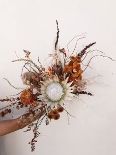 Gorgeous boho autumn bridal bouquet with orange tones, rust orchid, white protea, and pampas  #fall #wedding #bride #bridalbouquet #uniqueweddings #weddingflowers