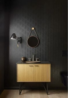 With black wallpaper and a beautiful wood floor, this powder room features a wall-hung toilet, mid-century modern vanity and artisan sink. Mid Century Modern Vanity, Mid Century Modern Design, Steel Building Homes, Bathroom Design Inspiration, Colour Inspiration, Bronze Bathroom, Master Bathroom, Wall Hung Toilet, Contemporary Bathroom Designs