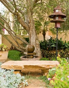 Shaded by a melaleuca tree, the bench was created out of rock left from the home's construction.