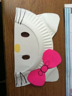 DIY Hello Kitty paper plate masks.  Cut paper plate in half. Leave one half alone for the head. The other half cut into 4 even pieces, like pizza slices. Round the edges. You only need two for the ears. Cut out a nose using yellow paper and glue. Cut out the eyes. Add a bow and glue the ears.