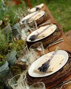 rustic elements, the greenery, the wicker chargers against the white plates, and adding a sprig of lavender place setting.