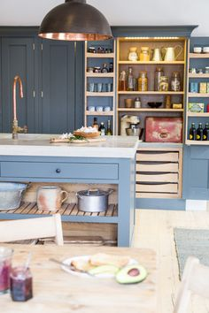 View across centre island with concrete worktop to bespoke larder cabinet