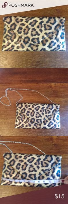 """Envelope Clutch Bag This envelope clutch bag features a tiger print design. It has a detachable chain that has approx a 21""""drop. The total length of the chain is approx 46""""s. The clutch is approx. 12""""s wide and approx. 6.5""""s tall. Only used twice and in excellent condition. No stains or flaws. It had a back zippered pocket and one pocket on the inside.  🌸BUNDLE 2 ITEMS FROM MY CLOSET AND SAVE 15%🌸 Bags Clutches & Wristlets"""