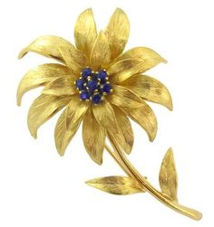 This is a gorgeous vintage 18k yellow pin by Tiffany & Co from the 1960's. The pin features beautiful Florentine gold finish flower motif that is enhanced by vivid blue sapphires that weigh approximately 0.40ct. The pin measures 57.5mm by 34mm and weighs 14.6 grams. The pin is stamped Tiffany & Co 18KT Italy.