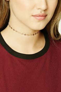 A high-polish choker featuring flat circles with tiny ornate cutouts and a lobster clasp closure.