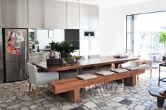 Love the stone flooring in the kitchen, the bench seating at the long dining table and the large open doors that lead out to the patio from the kitchen.