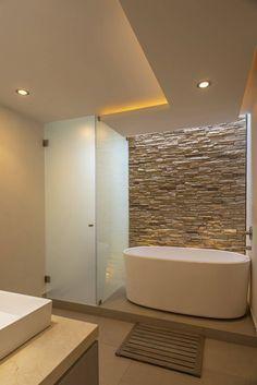 Bagno contemporaneo con vasca e box doccia - rivestimento in pietra - controsoffitti con luce diffusa