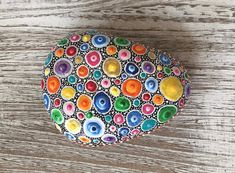 This beautiful rock was painstakingly and carefully hand painted using free form dotted art techniques. These can be practically used as a paper weight, and to enhance a coffee table display, mantels, window sills, book cases and other display areas. Every item is completely unique. Where
