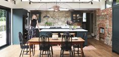 Old stone walls in a blue kitchen with brick fireplace | EKBB