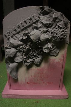 DIY headstone--styrofoam, artificial flowers, wood letters, all spray painted and then embellished.