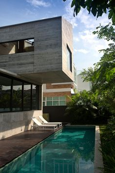 A concrete room cantilevers over a swimming pool as part of this extension to a postwar property in Singapore