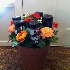 Father's Day Beer flower pot.  Bouquet in a flower pot. Directions: I weighted the pot down with bottled water, added florist foam, stuck the beer down in the foam, placed synthetic moss down and stuck silk flowers to add to the flower pot effect.