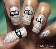 "DIY Halloween Mummy Nails with Tutorial and Video. If someone asked me what my favorite NAIL site was it would be My Simple Little Pleasures . Why do I love this site? Because she takes tons of great photos under different lighting conditions and labels them: """"natural' lamp"", ""camera flash"", ""shade"" etc... #halloween #diy #crafts #nails #mummy #mummies #nail_polish #nail_art #googly_eyes"