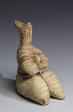"""Tel Halaf"" - Fertility Figurine - Syria - 5000-4000 BC - Terracotta w/traces of pigment -  As early as the 7th millennium BC, cultures in the Near East began to create organized settlements with well-developed religious and funerary practices.  The Halaf culture of Anatolia (central Turkey) and northern Syria arose around 5000 BC and produced remarkable female figurines with distinctive fertility attributes. This statuette is seated wlegs extended, her arms cradling her protruding…"