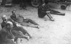 Five captured SS guards sit on the ground in the newly liberated Dora-Mittelbau concentration camp.  Date: Apr 1945