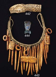 A NORTHWEST COAST SHAMAN'S NECK ORNAMENT | The hide-covered wood necklace suspending two bone masks, four bone rings, eighteen long cylindrical bone pendants and a central bone pendant with two bear's heads in relief, dark patina.