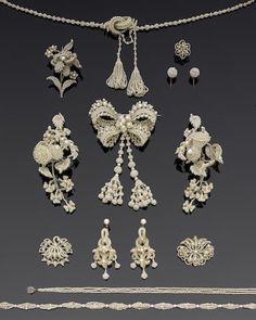 A collection of seed pearl jewellery, circa 1900. Including a large bow brooch with tassel drops, a pair of large foliate brooches with thistles mounted en tremblant, a pair of drop earrings with imitation pearl surmounts, three necklaces, one with a step-cut ruby and rose-cut diamond clasp, three further brooches, a pair of cluster earrings and a further single earring.