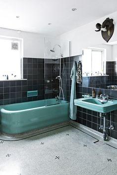 Badeværelset står næsten, som da huset blev bygget. De sorte klinker, det mintgrønne badekar, håndvasken og toilettet er originale, og kun armaturer er skiftet ud. Glasvæggen og spejlet er sat op af praktiske hensyn og bevidst lavet diskret, så det gamle kommer til sin ret.