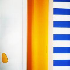 Dettaglio pittura a strisce navy, porta smaltata gialla, maniglia della serie PEDRA by C+ architettura
