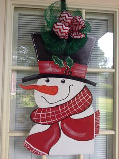 Front door decor Snowman door hanger door by samthecrafter on EtsyAnother snowman to greet your guest. The snowman measures 27 by including bow. This snowman can be personalized across his body or on hisSnowman Christmas ornaments are really popular Christmas Yard Art, Snowman Christmas Decorations, Christmas Wood Crafts, Christmas Snowman, Christmas Projects, Christmas Wreaths, Snowman Door, Door Hangers, Winter