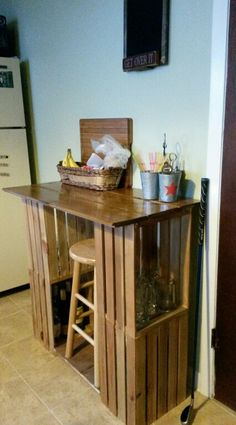 Bar/table made from wooden crates bought at Michael's and left over wood flooring which were then stained and sealed. Stacking the crates adds room for storage underneath making it great for small kitchen spaces or anywhere for entertaining!