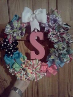 The wreath hairbow holder i made for all of my daughters hairbows. I took a styrofoam wreath, covered it in fabric then took ribbon and wrapped it around the wreath so that i could have a front row and top row of hairbows. Super easy and turned out really cute. I also added the painted S which you don't have to do, i just thought it was really cute!