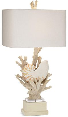 Make an elegant nautical statement with the Hanauma Bay Table Lamp from Kathy Ireland Home by Pacific Coast Lighting. Its bold coral and nautilus shell base sits on a pedestal of stacked squares, with a wide rectangular shade for contrast. Coastal Style, Coastal Decor, Natural Table Lamps, Love Wood Sign, Tropical Home Decor, Ireland Homes, Rustic Frames, Beach House Decor, Beach Houses