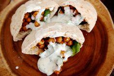 Een lekker vegan lunchrecept: pitabroodjes met curry kikkererwten, rauwkost en yoghurtsaus.