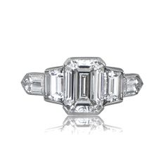 A beautiful Estate Emerald Cut Diamond Engagement Ring, accented by a tapered baguette and bullet-cut diamonds on either side.