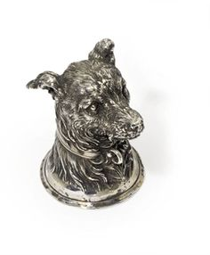 A silver stirrup cup in the form of a dog's head -  mark of Nicholls & Plincke, workmaster's intials PK, St. Petersburg, circa 1880 -  Realistically modelled as a terrier's head with a collar, reeded rim, gilt interior, marked on rim  3 1/8 in. (8 cm.) high