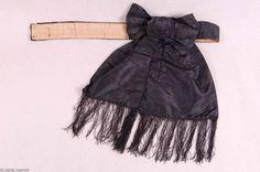 1860s black silk bow belt with fringe. Cotton back. ModeMuseum Provincie Antwerpen.