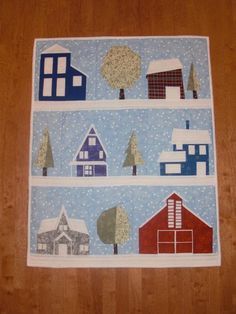 Country houses and buildings including a barn and many trees, semi-wonky quilt.