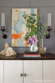 The entry sports a rosewood-topped buffet by Holly Hunt, sleek sconces by Jonathan Browning and a colorful painting by Tristan Govignon.