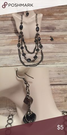 Navy blue stone necklace and matching earrings Dark grey colored chain with multiple strands of large navy blue semi metallic stones covered with thin white markings, which look like very thin paint splatters. Matching drop down earrings. Jewelry Necklaces