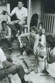 A young Bob Dylan plays on the back of the SNCC office in Greenwood, Mississippi in 1963.