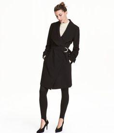 Schwarz. Mantel aus festem Webstoff mit drapiertem Revers. Der Mantel hat ein Gürtel mit Metallschnalle und seitliche Taschen. Ärmelriegel mit Druckknöpfen