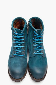 DSQUARED2 //  Teal Brushed Leather Hiking Boots  32148M047012  Ankle-high brushed leather boots in teal. Round toe with distressed effect. Bright blue lace up closure with silver tone eyelets. Zip closure at inner side. Logo rivet, embossed logo and white stitch detail at collar. Paneled upper. Brown foxing. Lug sole. Tonal stitching. Leather upper, rubber sole. Made in Italy.  $685 CAD