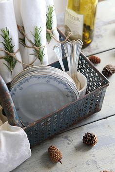 rosemary sprigs. white napkins. blue china. pine cones.