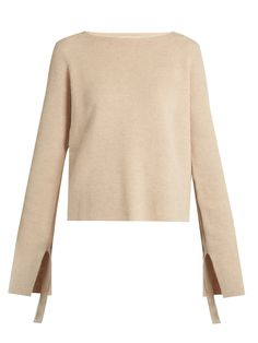 Helmut Lang is synonymous with pared-back sophistication. This beige ribbed wool and cashmere-blend sweater encapsulates this aesthetic, styled with a round neck and slit cuffs. Layer it over a silk blouse, pulling the ribbon inserts to nonchalantly ruche the sleeves