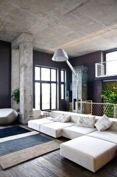 decoração sala de estar no estilo industrial com sofá branco moderno, piso de madeira e teto de concreto