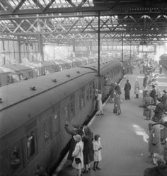 London, 1944: On a busy platform at London's Euston station, women and children wave goodbye to their loved ones. In the foreground, a group of two women and two children can be seen waving to someone at the window of the carriage,and further down the platform, a soldier leans out of the window to give his girlfriend one last kiss. Scenes such as this are repeated down the length of the train, whilst other servicemen and women (including a WAAF, centre), await their own trains.