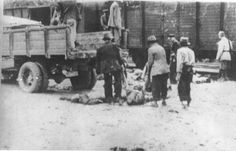 Under the supervision of Romanian guards, Gypsies load the corpses of victims of the Iasi-Calarasi death onto trucks in Targu-Frumos