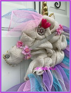 Magical Unicorn for your kids room! Perfect for that child that just LOVES Unicorns! This Unicorn, is made with a white burlap body, and the mane is accented with lavender, pink, turquoise, and white with gold and silver threaded mesh. This is sure to be a hit with your child! This is a Made to Order wreath, so please allow 3-4 weeks for delivery. Can customize to any color mane that you would like. If you are local to Marlette, MI type in LOCAL10 in the coupon section to waive the shipping…