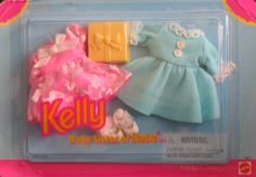 """Barbie Kelly Party Fashions (1996). Kelly, Baby sister of Barbie Doll Fashions is a 1996 Mattel production. Includes: pink Party Dress w/iridescent bow at neck & sheer pink w/white & blue pattern over-skirt, blue Party Dress w/white lace cuffs & collar & 2 small white buttons on top, Pair of white Socks w/lace trim at cuffs, Pair of white Shoes, & a yellow plastic Gift Box. Included items intended & fit most Kelly & other 4.5"""" fashion size dolls; dolls NOT included. For Ages 3+ Years. All..."""