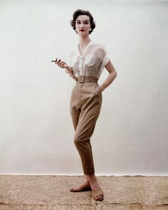 Evelyn Tripp wearing khaki beige pants with built-in belt with boned camisole in matching cotton gabardine and a shirt of transparent white organdy, all by Loomtogs, gilt bracelets by Bergere, flat mules by Capezio, 1953