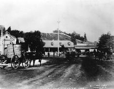 Horses and buggies at the Los Angeles Plaza in 1888. The California Bakery is seen in the background, as well as a covered wagon advertising the Home Ice Company. A horse and buggy in the foreground advertises for Bluett & Sullivan at 1st and Spring streets. Fort Moore Hill can be seen in the background.