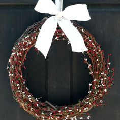 This primitive Christmas wreath features red, white and green pip berry garland, securely attached to a grapevine base, to give your front door a beautiful country primitive look for the holiday season. Also great for hanging above a mantel, on an old mirror and more. Your wreath will be handmade to order, and finished off with a bow in your choice of color.