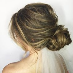 @sunkissedandmadeup A knotted bridal updo with a pretty little veil tucked underneath